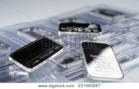 Minted Silver Bars Weighing One Troy Ounce In Plastic Packaging And Unpacked. Selective Focus. Feinz