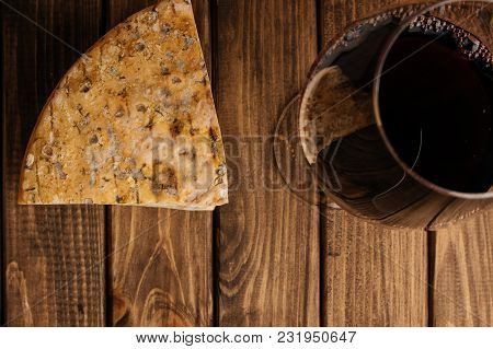 Cheese With Edible Mildew And Glass Of Red Wine On Wooden Brown Background