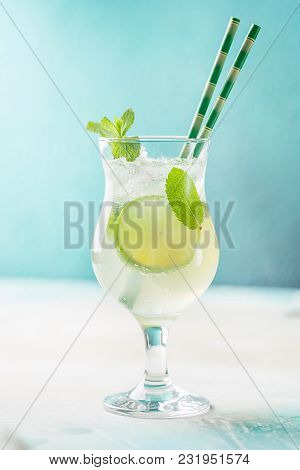 Mojito Cocktail With Lime And Mint In A Cocktail Glassover Blue Background.
