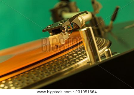 Closeup of turntable needle on roange vinyl record, tilted view