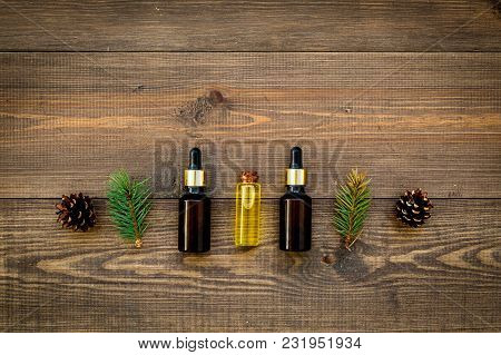 Pine Spa Cosmetics, Products For Skin Care. Fir Essential Oil Near Branches And Cones On Wooden Back
