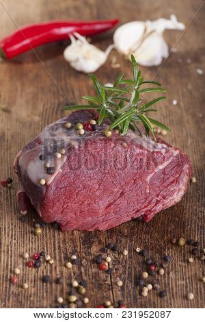 Overview Of A Raw Steak On Wood With Pepper