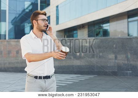 Attractive Concerned Businessman In Eyeglasses Is Talking On Cell Phone, Drinking Coffee And Gesturi