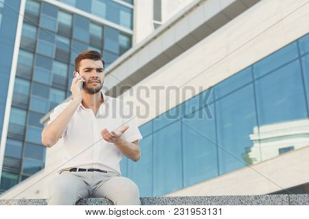 Attractive Confused Businessman Is Talking On Cell Phone While Sitting On Parapet Near A Modern Offi