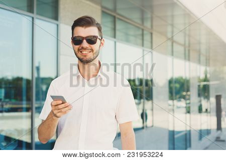Attractive Happy Businessman In Sunglasses Is Texting On Cell Phone While Standing Near A Modern Off
