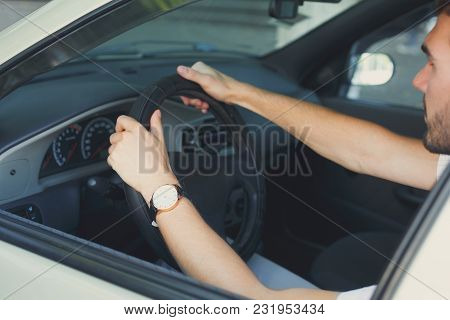 Closeup Of Male Hands Holding The Steering Wheel. Unrecognizable Businessman Sitting In Car On Drive