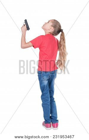 Young Girl Is Standing With Her Back To The Camera And Aiming A Gun Up, Isolated On A White Backgrou