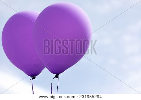 Two Purple Helium Balloons Against A Blue Sky Horizontal Photo