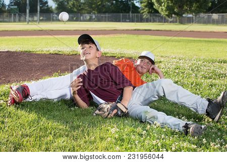 Two Boys In Baseball Jerseys Relaxing On The Grass At A Baseball Field.
