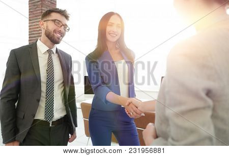 two beautiful businesswomen handshaking in office