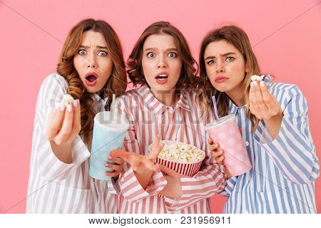 Three fascinating girls in homewear eating pop corn and drinking soda from paper cups during watching thrilling and exciting movie at home party isolated over pink background