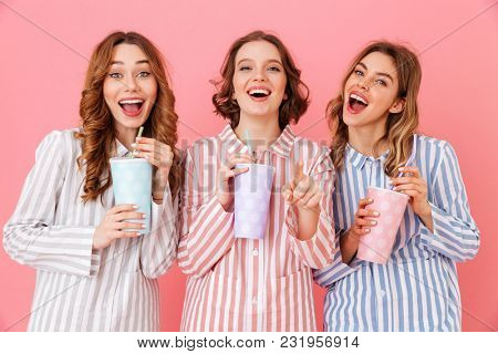 Three beautiful young girls 20s wearing colorful striped pyjamas smiling and drinking cold soda from paper cups during happy sleepover isolated over pink background