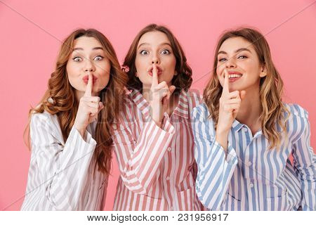 Beautiful young girls 20s wearing colorful striped pyjamas having fun and holding index fingers on lips asking to keep secret during sleepover isolated over pink background