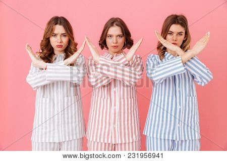 Portrait of three beautiful young girls 20s wearing colorful striped pyjamas showing crossed hands no gesture meaning deny at home party isolated over pink background