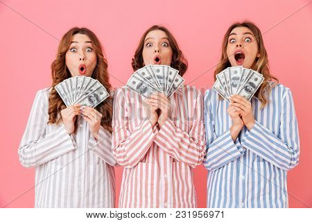 Photo of lovely teen girls 20s in colorful striped pyjamas holding fans of money dollar bills and smiling on camera at slumber party isolated over pink background