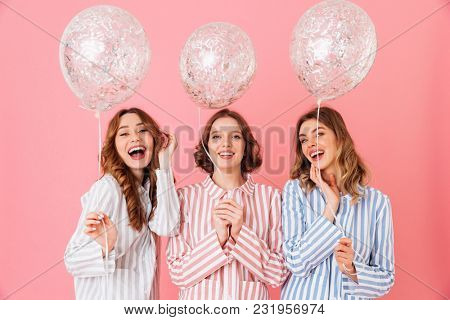 Photo of lovely teen girls 20s in colorful striped pyjamas holding air balloons and smiling on camera at slumber party isolated over pink background
