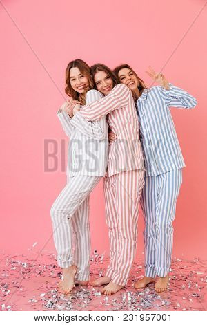 Full length photo of three beautiful smiling teenage women 20s wearing leisure clothings hugging together and enjoying sleepover isolated over pink background