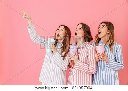 Three content women with good mood in striped pyjamas smiling and looking upward on copyspace while drinking soda from paper cups at home isolated over pink background