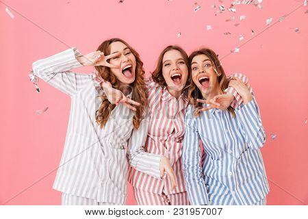 Three happy women 20s wearing leisure clothings hugging and having fun at slumber party while showing victory sign isolated over pink background