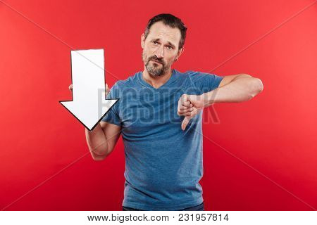 Disappointed adult guy 30s holding blank speech arrow pointer directing downward on copyspace and showing dislike gesture isolated over red background