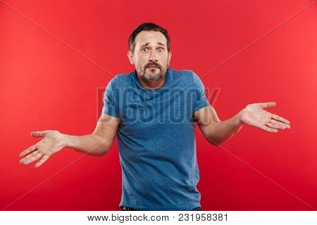 Portrait of caucasian adult man looking at camera expressing misunderstanding with throwing up hands isolated over red background