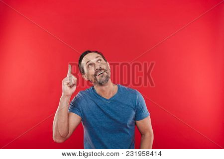 Happy unshaved man 30s in casual blue t-shirt smiling and pointing finger upward on copyspace closeup isolated over red background