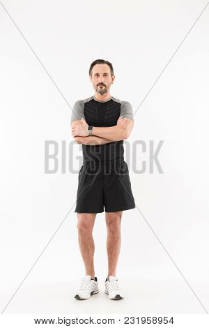 Full length portrait of a confident mature sportsman standing with arms folded and looking at camera isolated over white background