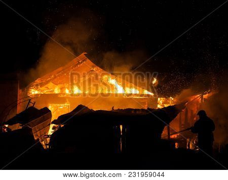 Arson or nature disaster - firefighter at burning fire flame on wooden house roof