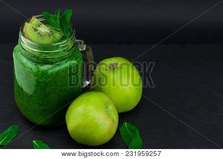 Green Smoothie With Fruits And Vegetables On Black Background. With Copy Space.