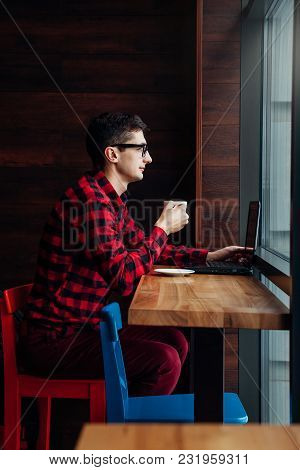 Young Businessman Enjoys Coffee In The Cafe Talking On The Phone And Using A Laptop In Front Of The