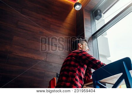 Young Handsome Man Enjoys Coffee In The Cafe In Front Of The Window