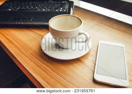 Drinking Coffee While Using A Laptop In Cafe. Cup Of Coffee With Glasses And Laptop In Font Of The W