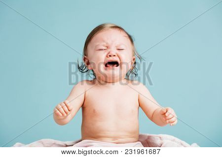 Sad baby sitting down and crying. Blue background. Whiny, weeping expression.