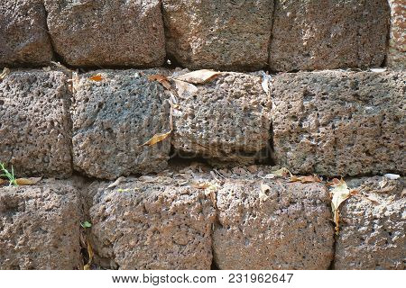 Background Textured Of Red Laterite Brick Stones Wall. Laterite Is A Soil And Rock Type Used As Buil