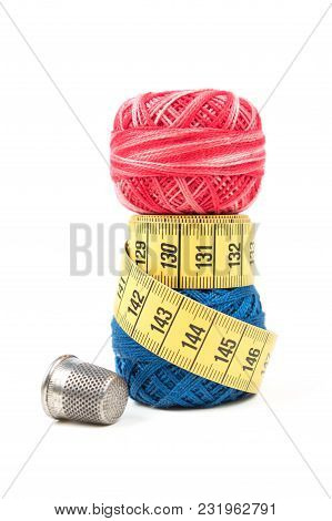 Yellow Measuring Tape On Top Of Blue Sewing Thread With Silver Thimble On A White Background. Red Se