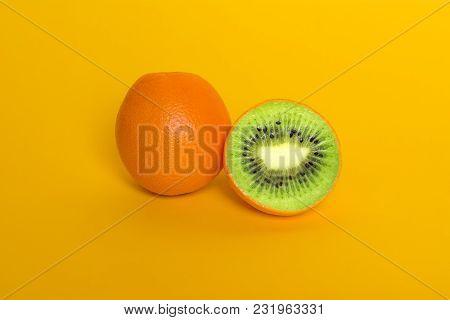 Collage orange with kiwi. Orange on yellow background. Surrealism fruits. Genetically modified food GMO poster