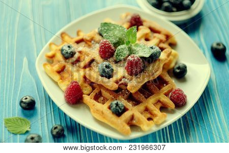 Belgian waffles with blueberries, raspberries and powdered sugar on wooden table.