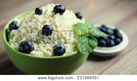 Cottage cheese and blueberry in a bowl on a table. Good breakfas