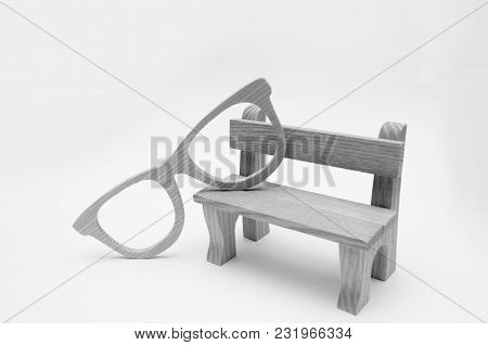 Concept Of Old Age, Wooden Model Bench  With Wooden Glasses On A White Background, Wisdom, Contempla