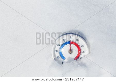 Thermometer with celsius scale placed in a snow showing zero temperature spring weather concept