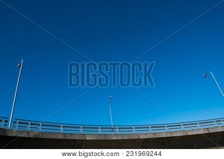 Highway over pass or  raised road with lamppost under a deep blue sky.