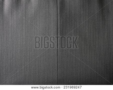Black or dark grey pinstripe or chalk stripes suit or slacks background macro.