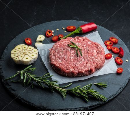 Raw ground beef meat burger steak cutlet with chili, rosemary and garlic on black slate plate for cooking