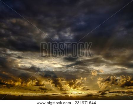 Dramatic sky with sun rays seep through clouds during sunset