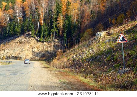 road with sign in mountains and autumn forest