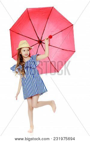 A Stylish Little Girl With Long Blond Hair In A Very Short, Striped, Summer Blue Dress And A Straw H