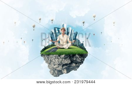 Man In White Clothing Keeping Eyes Closed And Looking Concentrated While Meditating On Flying Island