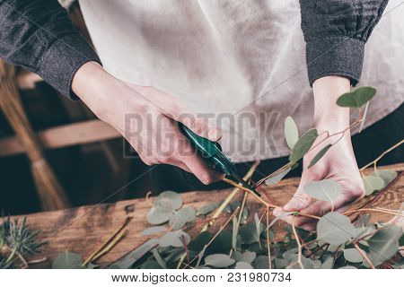 Florist At Work On Arragment Flower Bouquet On A Wooden Table