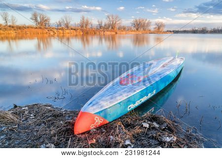 Fort Collins, CO, USA - March 17, 2018: Racing stand up paddleboard laying upside down on a shore of a calm lake at dusk - 2018 model of All Star SUP by Starboard.