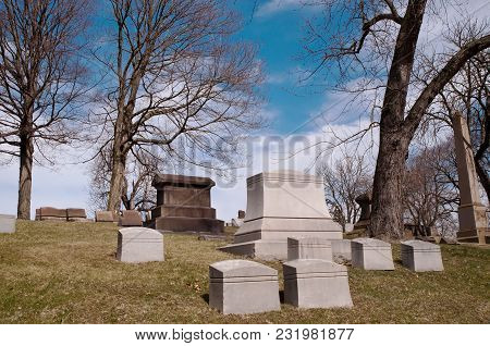 Gravestones On A Hillside In A Cemetery With Bare Winter Trees Behind It Along With Bright Blue Skie